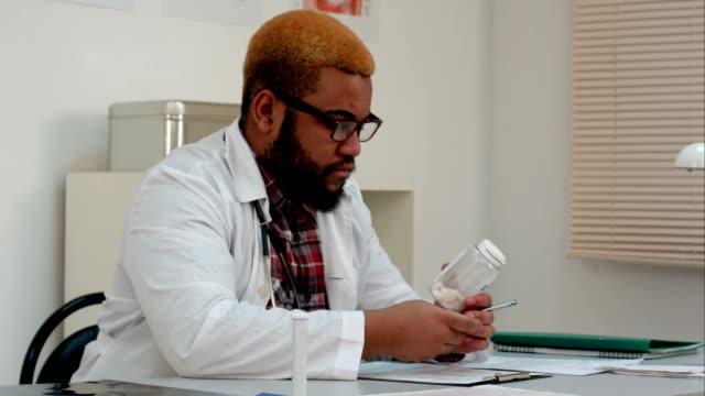 African-american-male-medical-worker-prescribing-pills