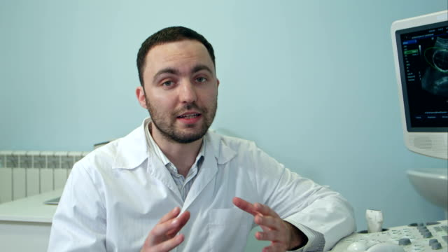 Joven-médico-masculino-hablando-a-la-cámara-sentado-junto-a-la-máquina-de-exploración-del-ultrasonido