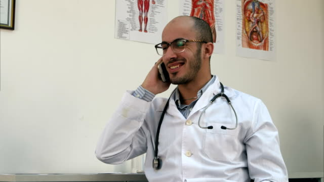 Smiling-male-doctor-having-a-cheerful-phone-conversation