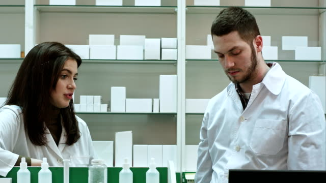 Two-adult-pharmacists-having-conflict-discussing-problems-at-pharmacy