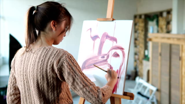 Woman-paints-swift-strokes-of-pink-flamingos-in-different-angles-she-uses-brush