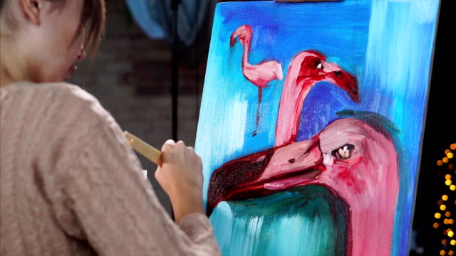 A-young-artist-paints-a-painting-with-oil-paints-with-a-flamingo