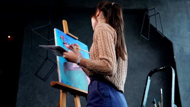 The-girl-paints-flamingos-in-pink-the-picture-is-on-the-easel-in-the-studio