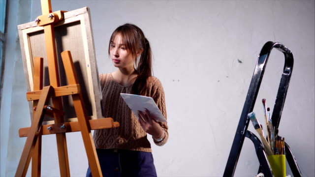 Young-woman-paints-oil-paints-on-canvas-in-art-space-with-large-windows