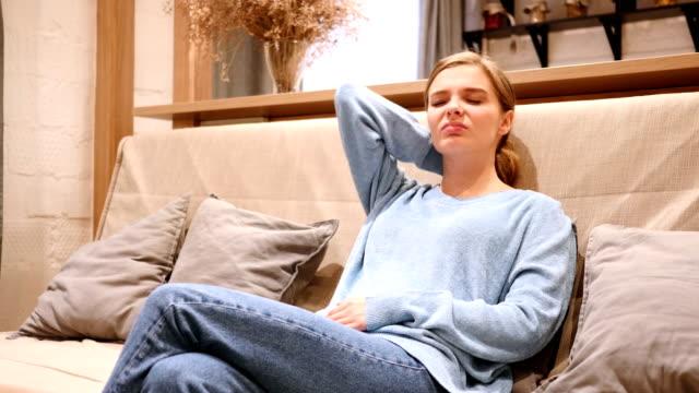 Mujer-con-dolor-en-el-cuello-tratando-de-relajarse-en-el-sofá-en-casa