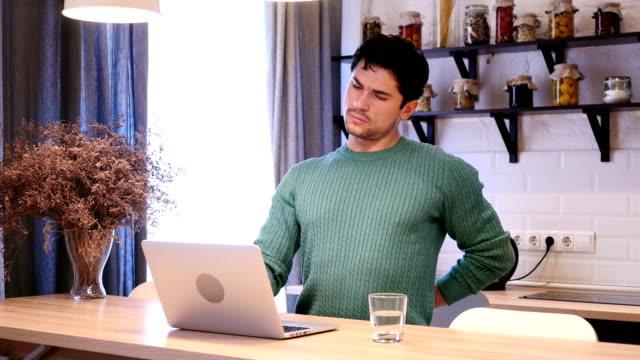 Hombre-joven-con-dolor-de-espalda-trabajando-en-ordenador-portátil-en-la-cocina