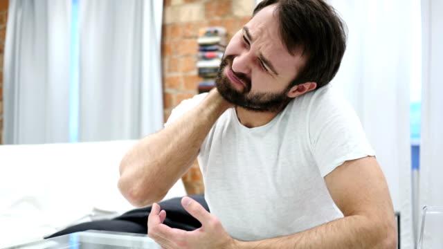 Dolor-de-cuello-hombre-de-barba-cansado-sentado-en-casa