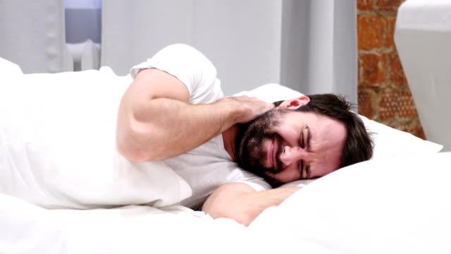 Hombre-de-barba-con-dolor-en-el-cuello-tratando-de-relajarse-en-la-cama