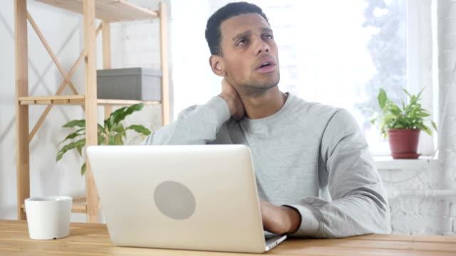Dolor-de-cuello-hombre-afroamericano-cansado-sentado-en-el-trabajo