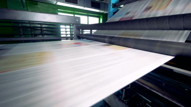 Tira-del-periódico-en-una-máquina-de-impresión-Vista-detallada-de-una-máquina-de-impresión-en-acción-Periódicos-pasando-junto-a-la-cámara-