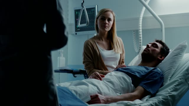 In-the-Hospital-Patient-Lying-in-Bed-his-Wife-Sitting-Beside-the-Sick-Man-Listens-to-Doctor-s-Explanations-Love-and-Care-Concept-