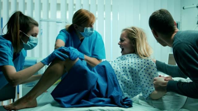 En-la-mujer-del-Hospital-en-trabajo-empuja-a-dar-a-luz-obstetras-a-marido-sostiene-su-mano-Entrega-moderna-sala-con-parteras-profesionales-