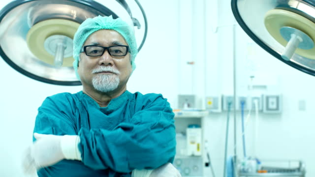 Médico-Senior-mirando-a-cámara-con-sonrisa-en-la-sala-de-operación-Salud-y-médica-concepto-