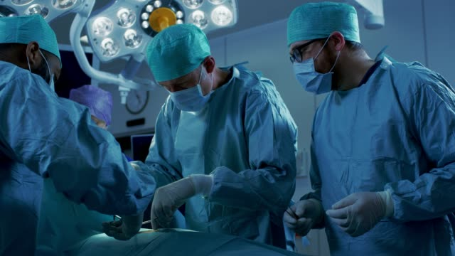 In-the-Hospital-Operating-Room-Diverse-Team-of-Professional-Surgeons-and-Nurses-Suture-Wound-after-Successful-Surgery-