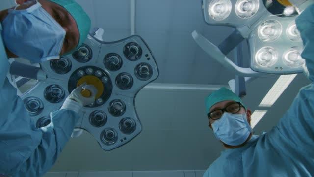 Bajo-ángulo-de-disparo-paciente-visión-POV:-dos-profesionales-cirujanos-encender-lámparas-de-cirugía-y-flexión-sobre-el-paciente-