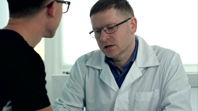 Male-doctor-in-glasses-consulting-male-patient