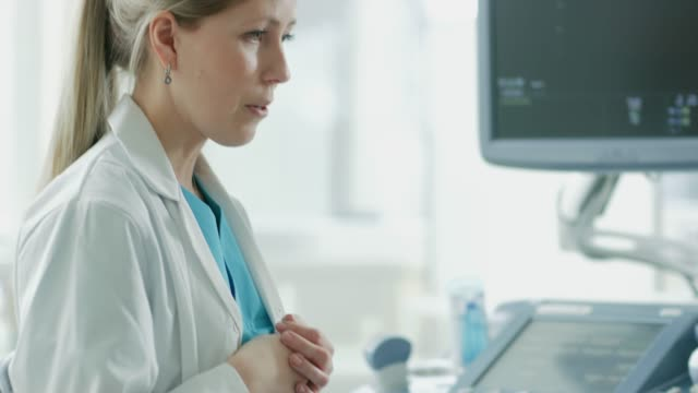 In-the-Hospital-Pregnant-Woman-in-Bed-Has-Ultrasound-/-Sonogram-Procedure-Friendly-Obstetrician-Explains-Details-