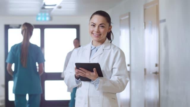 Schöne-junge-Frau-Doktor-steht-auf-dem-Krankenhaus-Flur-Tablettcomputer-benutzt-und-lächelt-charmant-Professionelle-Leute-bei-der-Arbeit-