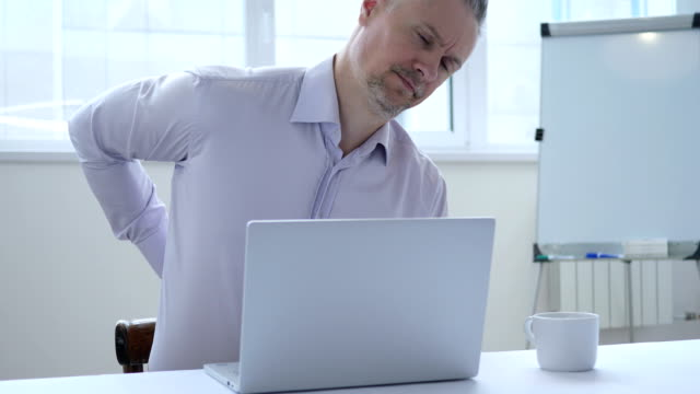 Middle-Aged-Businessman-with-Spinal-Back-Pain-Working-in-Office