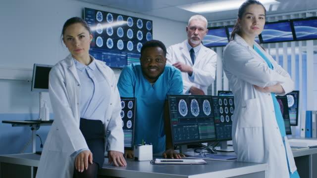 Diverso-equipo-de-científico-médico-posando-con-cruzó-los-brazos-en-el-laboratorio-de-alta-tecnología-Sceince-del-cerebro-/-centro-de-Neurología-investigación-laboratorio-con-múltiples-Dispalys-mostrando-TC-/-IRM-imágenes-