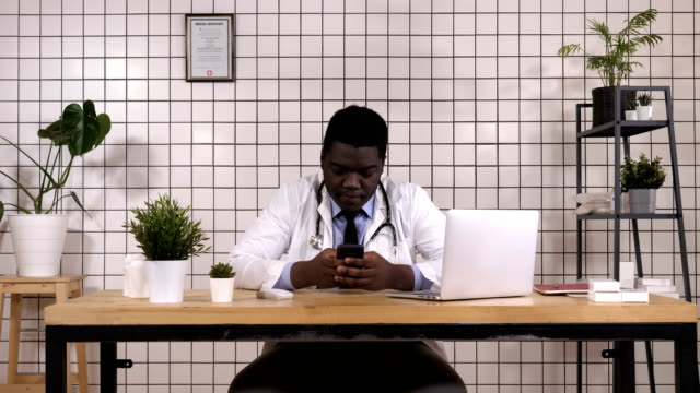 African-American-Doctor-Holding-Smart-Phone-Texting