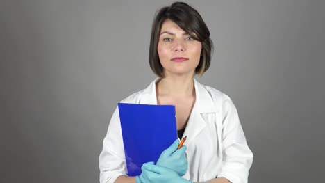 Friendly-young-nurse-holding-folder-isolated-on-grey-background-Healthcare-concept-Shot-in-4k-