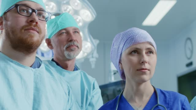 Gliding-Shot-of-Diverse-Team-of-Professional-surgeon-Assistants-and-Nurses-Standing-Proudly-in-the-Real-Modern-Hospital-with-Authentic-Equipment-