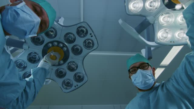 Low-Angle-Shot-POV-Patient-View:-Two-Professional-Surgeons-Turning-on-Surgery-Lights-while-Bending-over-Patient-
