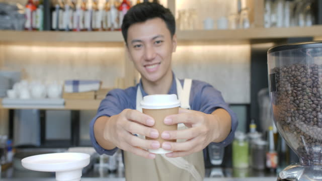 Coffee-Business-Concept---Beautiful-Caucasian-lady-smiling-at-camera-offers-disposable-take-away-hot-coffee-at-the-modern-coffee-shop