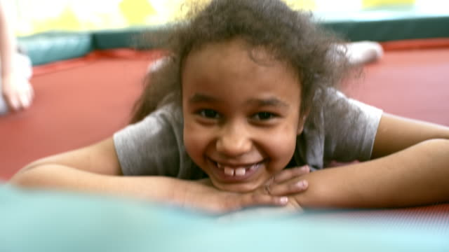 Black-Girl-Lying-on-Trampoline-and-Smiling