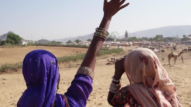 Tilt-up-on-the-back-of-friends-waving-and-talking-at-Pushkar-Mela-festival