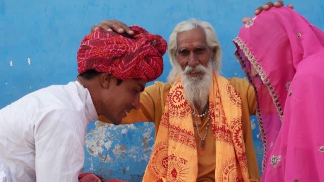 Hindu-Sadhu-blessing-a-newly-wed-couple-in-traditional-dress-everyone-looking-at-camera