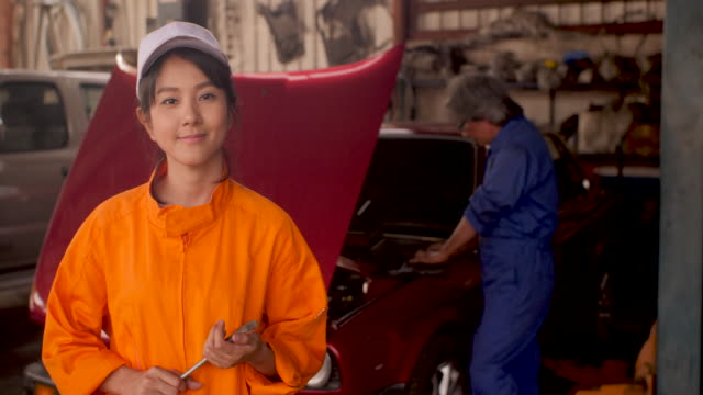 Portrait-of-a-young-beautiful-car-mechanic-in-a-car-workshop-in-the-background-of-service-car-service-concept-dolly-shot