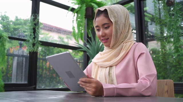 Beautiful-young-smiling-asian-muslim-woman-using-tablet-sitting-in-living-room-at-home-Enjoying-time-at-home-