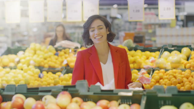 At-the-Supermarket:-Portrait-of-the-Beautiful-Smiling-Woman-Standing-in-the-Fresh-Produce-Sectiomn-of-the-Store-Choosing-Organic-Fruits-and-Vegetables-