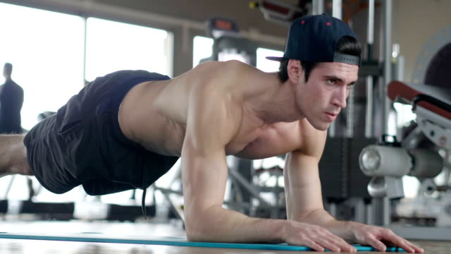 A-shirtless-guy-at-the-gym-trains-his-body-to-stay-fit-and-have-defined-muscles-The-athlete-raises-heavy-weights-and-fatigue-