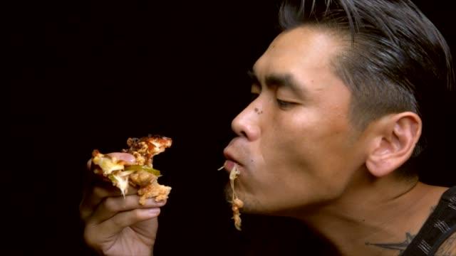 hombre-tatuado-asiático-lenta-come-vorazmente-una-rebanada-de-pizza