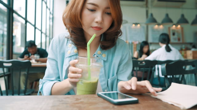 Cheerful-happy-asian-young-woman-sitting-drinking-iced-green-tea-in-cafe-using-smartphone-for-talking-reading-and-texting-Women-lifestyle-concept-