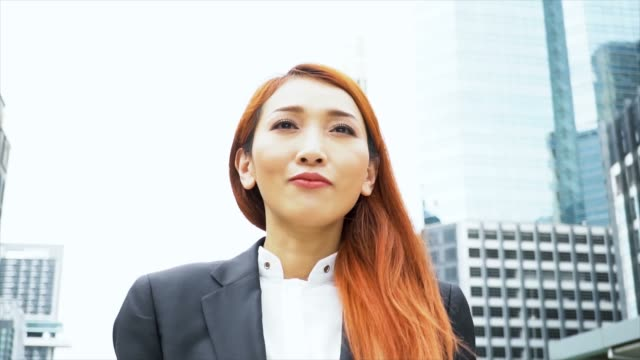 Close-up-tracking-shot-of-Young-attractive-Asian-business-woman-walking-in-the-urban-city-background