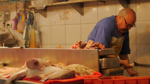 A-hispanic-man-weighs-fish-in-a-fish-market-in-Mexico