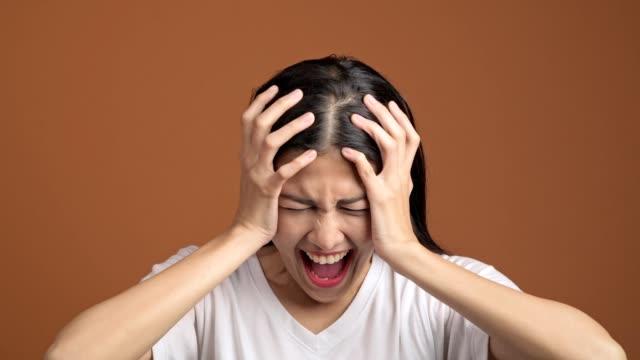 Mujer-enojada-aislada-Retrato-de-mujer-asiática-en-blanco-camiseta-gritando-en-voz-alta-mirando-a-cámara-y-de-la-mano-en-la-cabeza-