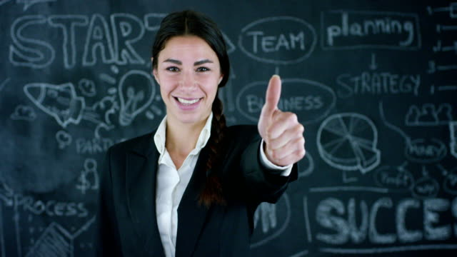 Beautiful-business-girl-marketing-teacher-draws-a-graph-of-success-on-a-black-board-on-a-black-background-