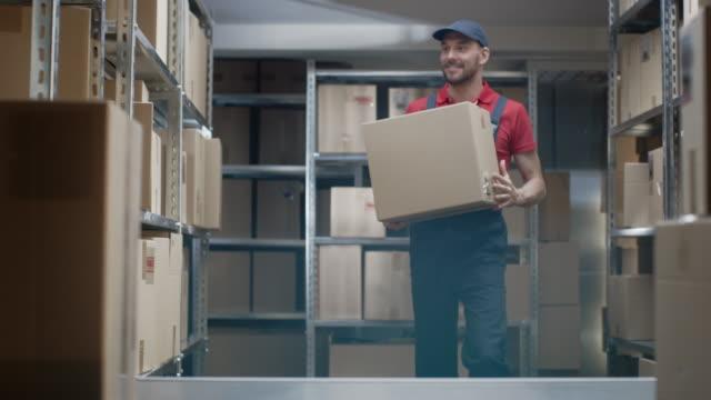 Trabajador-almacén-entra-en-almacén-con-una-caja-de-cartón-y-pone-en-un-estante-