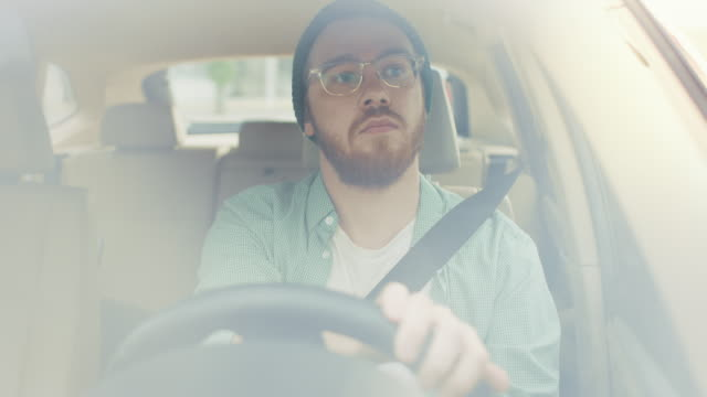 Portrait-of-Stylish-Young-Man-Drives-a-Car-through-big-Sunny-City-makes-a-Turn-Camera-Shot-Made-From-the-Front-Windshield-