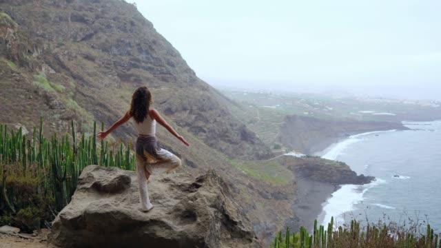 Mujer-joven-medita-en-la-cima-de-la-montaña