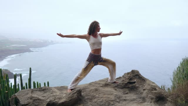 Young-woman-doing-yoga-on-a-rocky-seashore-at-sunset-The-concept-of-a-healthy-lifestyle-Harmony-Human-and-nature-The-background-of-the-blue-ocean-