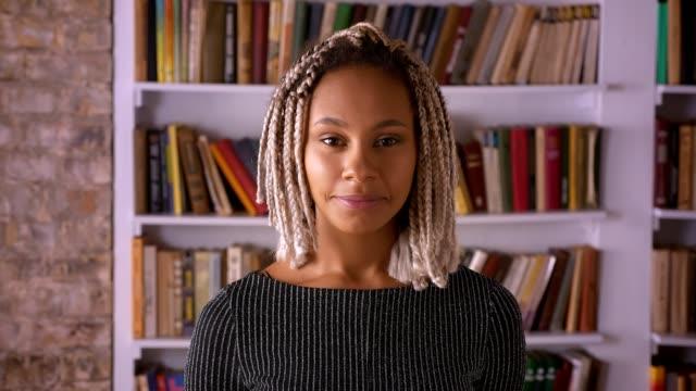 Chica-joven-africano-con-rastas-sonriendo-y-mirando-a-cámara-estantes-para-libros-en-el-fondo