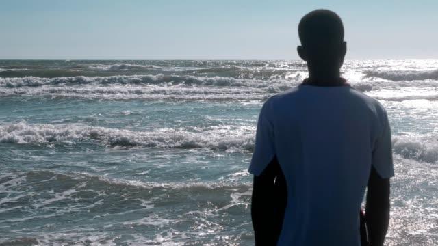 Afrikanischer-Mann-allein-das-Meer-zu-betrachten-Migration-Meer-Hilfe