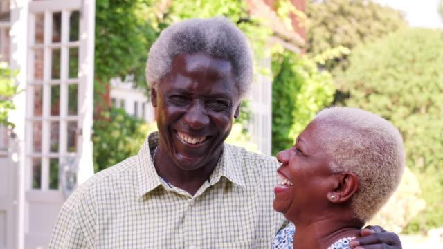 Senior-pareja-negra-abrazándose-y-sonriendo-en-un-jardín