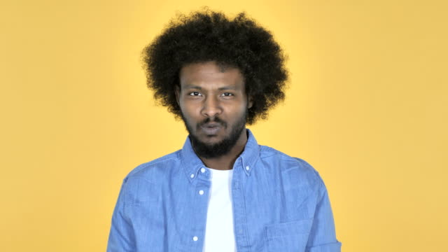 Afro-American-Man-Shaking-Head-to-Reject-on-Yellow-Background